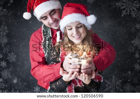 Boy give a Christmas gift to her girlfriend. Happy young couple wearing Santa hat.Magic card.