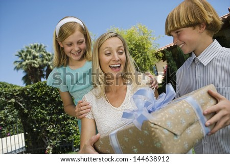 Boy giving birthday present to his surprised mother with a girl outdoors