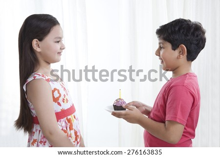 Boy giving cupcake to a girl