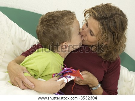 Boy giving his Mothers Day present to his mother. Mother is kissing the boy.