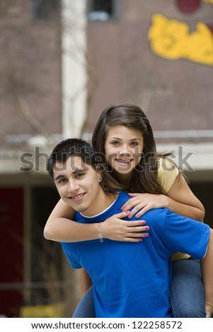 Boy giving piggyback ride to his girlfriend outdoors