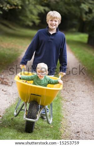 Boy giving toddler ride in wheelbarrow along path