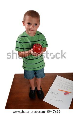 Boy going back to school holding apple standing on desk