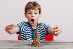 Boy grabbing to take stack of money coins.