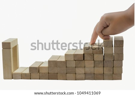 Boy hands, wooden blocks on a white background. Finger gestures up and down with abstract ideas in the world of business competition. #1049411069