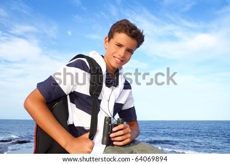 boy handsome teenager summer binoculars explorer in blue beach
