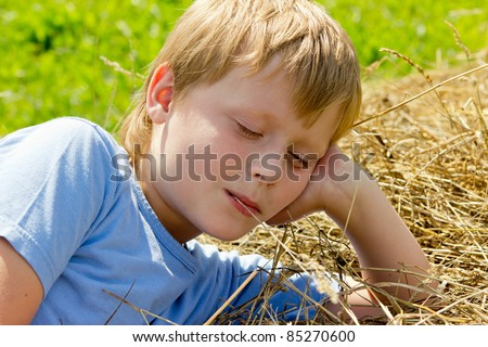 Boy have a rest on the haystack.