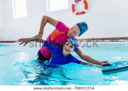 Boy having a swimming lesson with instructor #788923156