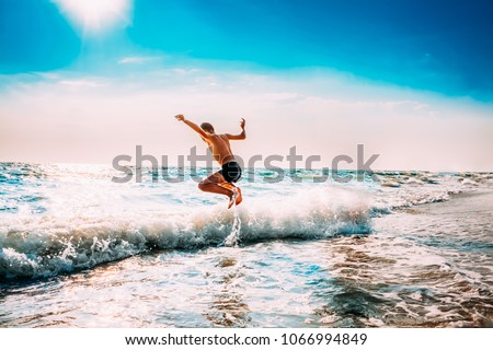 Boy Having Fun And Jumping In Sea Ocean Waves. Jump Accompanied By Water Splashes. Summer Sunny Day, Ocean Coast, Beach. Active Lifestyle And Recreation Concept. #1066994849