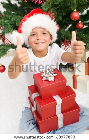Boy having lots of christmas presents showing thumbs up sign with both