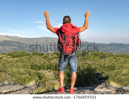 Boy hiking in the mountains at a tourist spot looking at the views and raising his arms