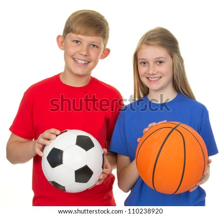 Boy holding a football and a girl holding a basketball, isolated on white
