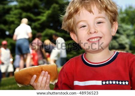 Boy holding a hot dog at a neighborhood picnic