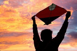 boy holding a paper kite above his head at dusk. Silhouette shows the kites flown during makar sankranti, independence day and uttarayan kite festival