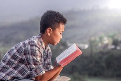 boy holding and reading the scriptures.