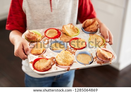 Boy holding baking tray, presenting the cakes he has baked to camera, mid section, close up