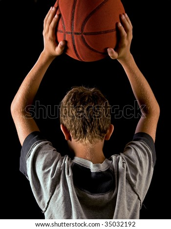 boy holding basketball over his head