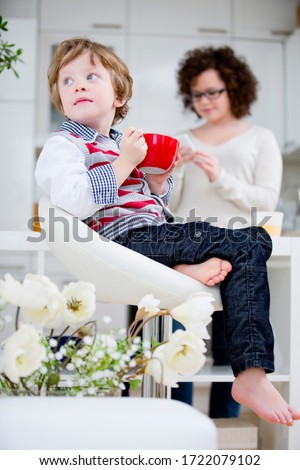Boy holding cup at home and looking away