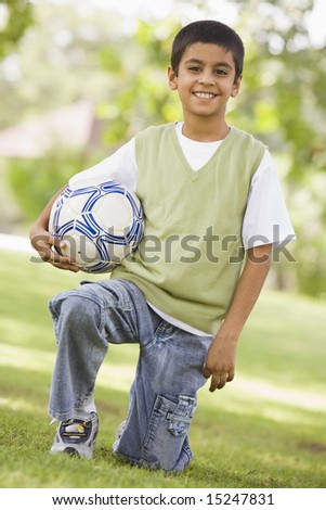 Boy holding football looking to  camera
