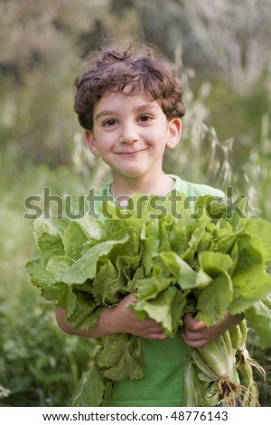 boy holding organic lettuce outdoors