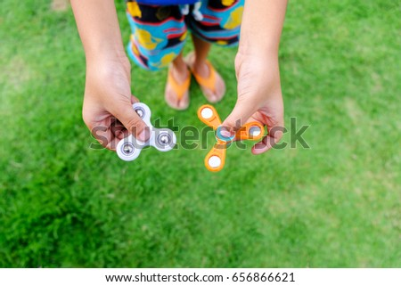 Boy holding play two fidget spinners, Fidget spinner white and orange color spinning stress relieving toy on green grass background.  #656866621
