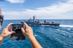 boy holds a phone and shoots a battleship in water.Mobile 4G and 5G internet services at high speed. using a mobile device such as a camera. keep and hold a cell phone.