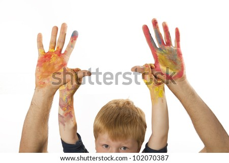 Boy holds the painted hands of his father