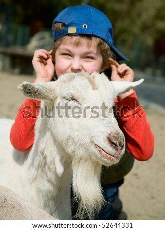 Boy hugging a goat on a platform for young