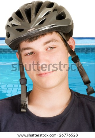 Boy in a bike helmet with the swimming pool in a background