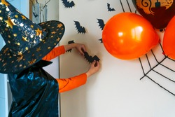 Boy in a black cape and a witch's hat glues a paper bat to the wall. The child decorates the house for Halloween.
