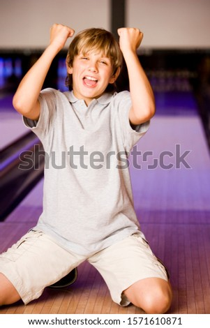 Boy in a bowling alley making victory salute