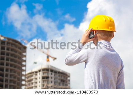 boy in a helmet and with toy portable radio introduces himself construction worker