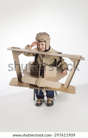 Boy in a pilots costume salutes. The action takes place near the cardboard airplane.