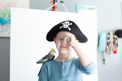 Boy in a pirate hat with a parrot on his shoulder