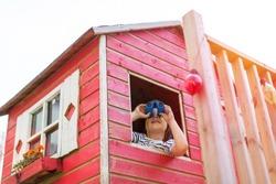 Boy in a wooden playhouse looking through a binocular