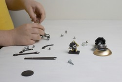 boy in a yellow t-shirt makes robots from metal parts on a white background