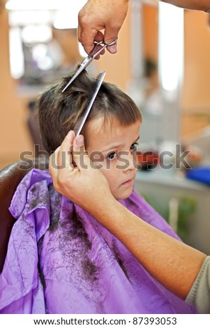 Boy in barbershop sad about loosing his hair