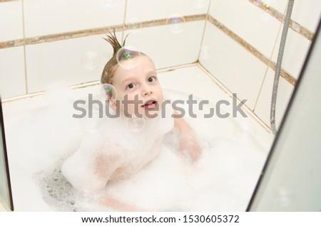 boy in bath  full of shower foam and soap bubbles.