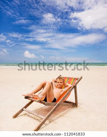 boy in beach chair on the beach