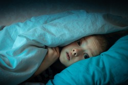 boy in bed with his eyes open. the child is afraid of the dark. tormented by nightmares and terrible dreams in children