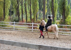Boy in black suit learning to ride a horse with a girl instructor. Girl leads the horse