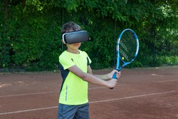 Boy in black VR glasses holding tennis raquet and learnes how to play tennis with virtual trainer. Sport in cyberspace.