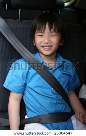 Boy in blue shirt fastening seat belt in the car