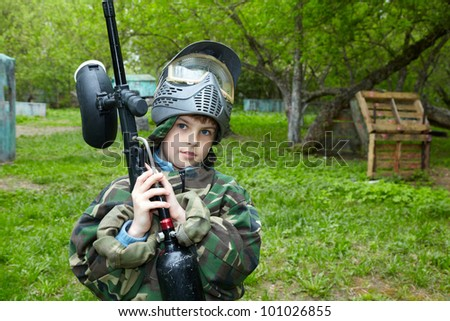 Boy in camouflage suit stands against the paintball area raising his paintball gun up and looks straight ahead