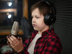 Boy in check shirt and headphone is singing or talking into microphone with pop filter in voice recording studio. Young singer recording his voice for phonogram performance for entertainment.