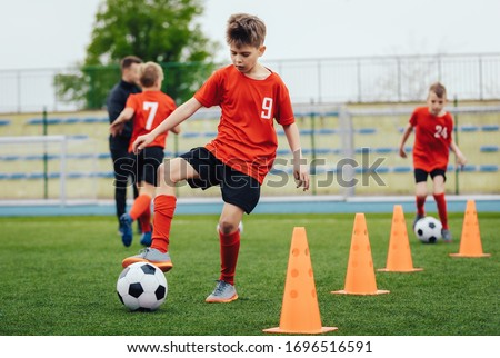 Boy in children's soccer team on training. Kids practicing outdoor with a soccer balls. Training football session for children on soccer camp. Young boy improving dribbling skills. Training with cones