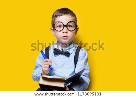 boy in glasses in a shirt and a butterfly, doing homework, on a yellow background