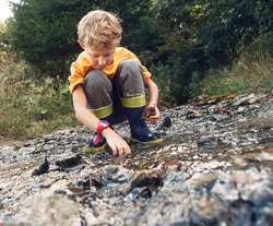 Boy in gum boots playing into the into te forest stream
