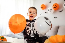 Boy in halloween costume playfully joy with his balloons. Kids trick or treat. Halloween.  Little boy in witch and skeleton costume. Halloween balloon blowing