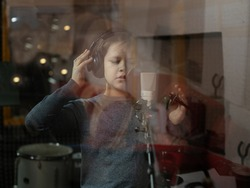 Boy in headphone is singing or talking into microphone with pop filter in voice recording studio. Young singer recording his voice for phonogram performance. View through the window in studio.